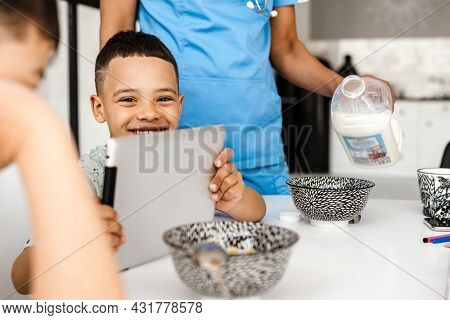Two boys using tablet computer while having breakfast at home
