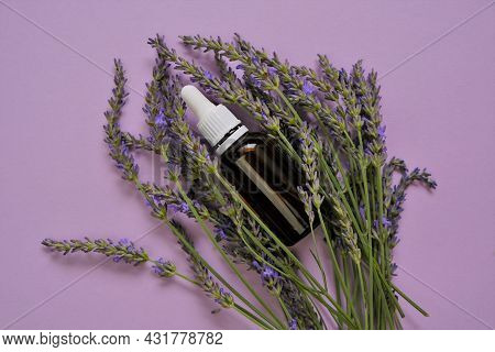 Lavender Essential Oil.glass Bottle And Lavender Flowers On A Lilac Background.organic Essential Oil