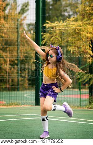 Girl Wearing Trendy Fashionable Sportswear And Rainbow Eyeglasses Dancing On Sports Ground. Fashion
