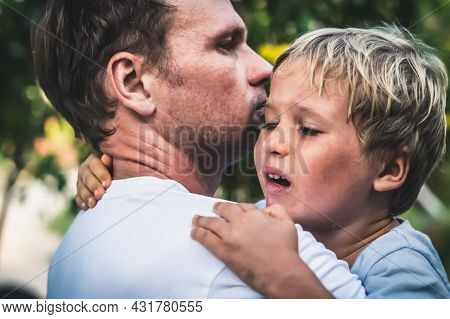 Closeup Sad Young Blond Boy Crying On Father Hands In Nature Park Outdoor. Man Holds Son, Hugs And C
