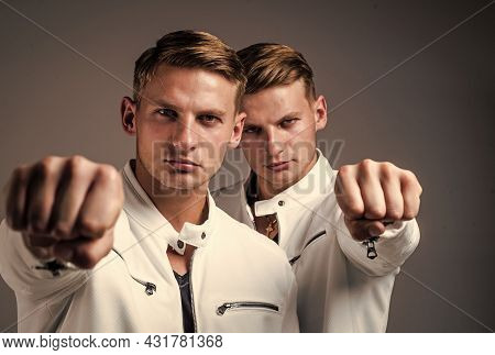 Young Twin Brothers With Similar Appearance Show Fist, Power