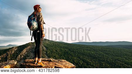 A Young Female Tourist With A Backpack Admires The Sunset From The Top Of The Mountain, Panorama. A
