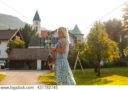 Young Woman Is Standing By Wooden Houses. Village In Mountains. Travel, Lifestyle Concept. Alps, Eur