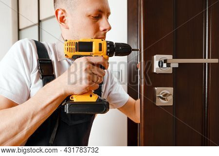 a man repairing a doorknob. Handyman repair the door lock in the room