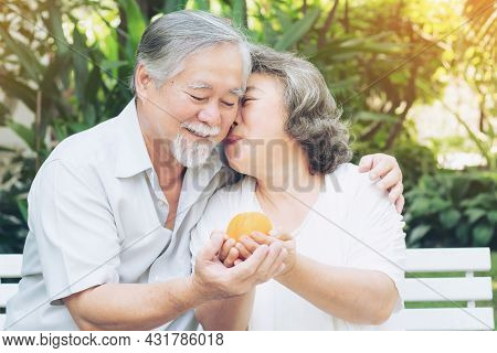 Retired Senior Couple , Husband Handing Fruit Then His Wife Kissed Him On The Cheek , Expressing Lov
