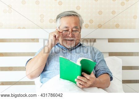 Senior Male , Elderly Man With Glasses Is Reading A Novel On Bed In His Bedroom - Lifestyle Senior E
