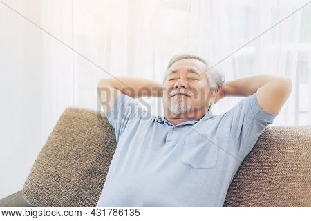 A Retired Old Man Smiling , Senior Man Relaxing On The Sofa In The Living Room At His Home - Lifesty