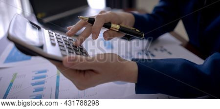 Businesswoman On Suit Hand Holding Pen And Press Calculator Button On The Desk With Paperwork At Wor