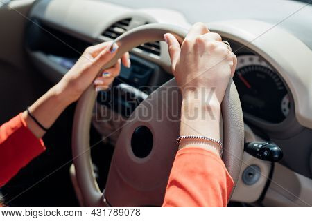 A Young Woman Is Sitting At The Wheel Of A Car. Transport Management.the Theme Of Traveling By Car.