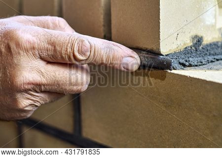 Bricklayer Builds New Fence From Facing Bricks. Alignment Of Inter-brick Joints