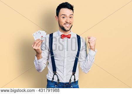 Hispanic man with beard holding poker cards screaming proud, celebrating victory and success very excited with raised arm
