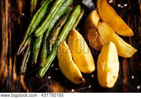 Baked Potatoes And Green Beans Are Served On Wooden Platter. Eating At The Restaurant. Vegetarian An