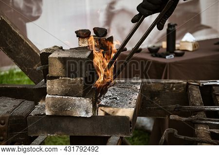 Blacksmith Takes Red-hot Metal Product Out Of The Fire With Tongs