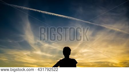 Silhouette Of A Girl Against The Sunset Sky. The Girl Stands With Her Back Against The Background Of