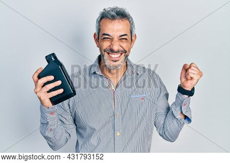 Handsome middle age man with grey hair holding motor oil bottle screaming proud, celebrating victory and success very excited with raised arm