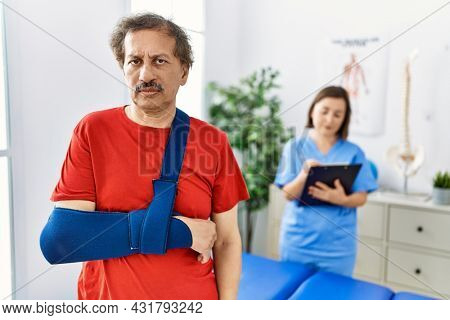 Southeast asian man wearing wearing arm on sling at rehabilitation clinic thinking attitude and sober expression looking self confident