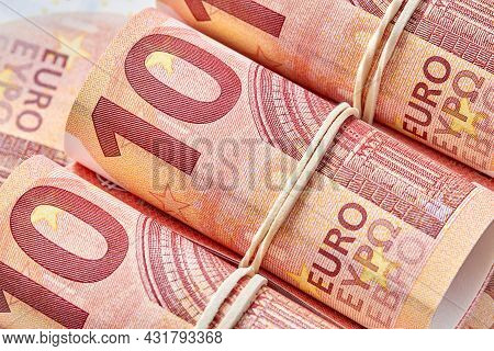 Ten Euro Bill Rolled Up As A Tubule. Ten Euro Banknote Details In A Macro Shot. Closeup, Selective F