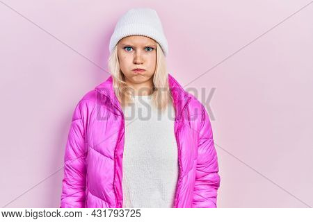 Beautiful caucasian blonde woman wearing wool hat and winter coat puffing cheeks with funny face. mouth inflated with air, crazy expression.