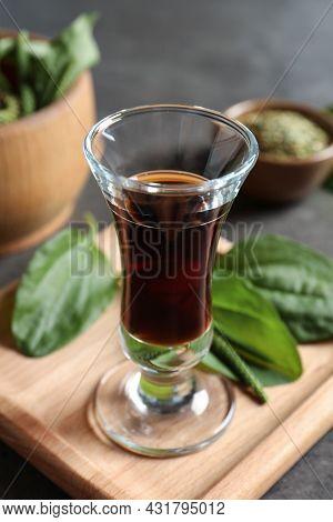 Glass Of Broadleaf Plantain Oil On Wooden Board