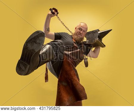 Bottom View Of Muscular Bearded Bald Man, Blacksmith In Leather Apron Or Uniform Isolated On Yellow