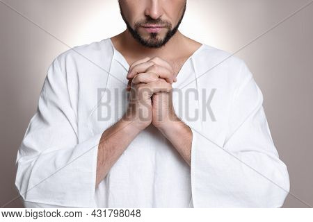 Religious Man With Clasped Hands Praying Against Grey Background, Closeup