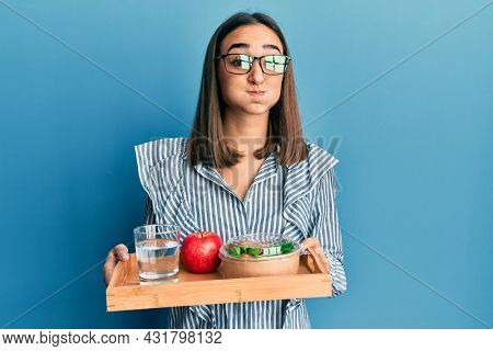 Young brunette girl holding tray with healthy lunch puffing cheeks with funny face. mouth inflated with air, catching air.