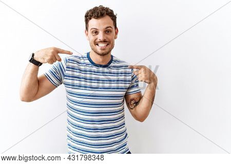 Handsome young man standing over isolated background looking confident with smile on face, pointing oneself with fingers proud and happy.