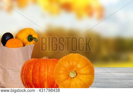 Closeup Of A Brown Paper Shopping Bag With Fresh Vegetables And Two Pumpkins On Table Over Abstract