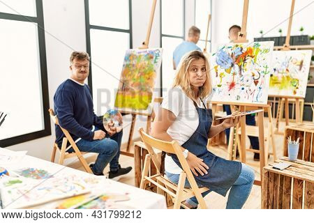 Group of middle age artist at art studio puffing cheeks with funny face. mouth inflated with air, crazy expression.