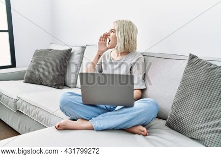 Young caucasian woman using laptop at home sitting on the sofa shouting and screaming loud to side with hand on mouth. communication concept.