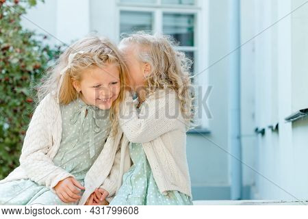 Two Little Cute Girls Are Sitting In The Garden And Sharing Secrets. One Girl Whispers Something In