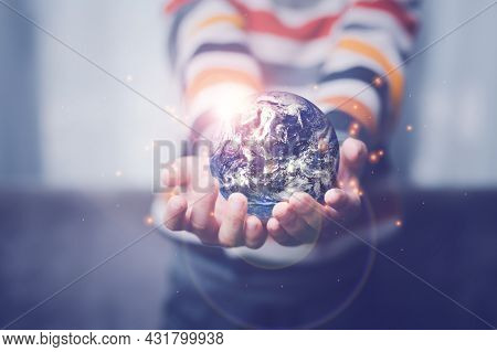 Boy's Hand Holding A Globe, The Globe In Children's Hands. Concept For Environment Conservation.
