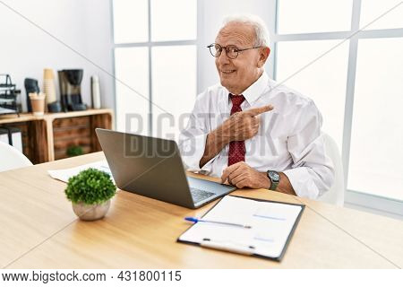 Senior man working at the office using computer laptop pointing aside worried and nervous with forefinger, concerned and surprised expression