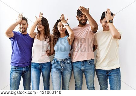 Group of young people standing together over isolated background surprised with hand on head for mistake, remember error. forgot, bad memory concept.