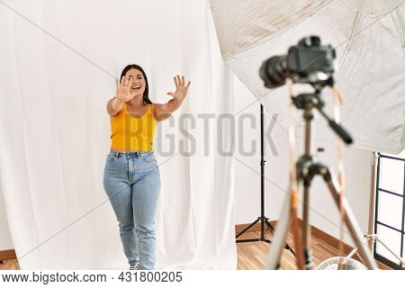Young beautiful hispanic woman posing as model at photography studio showing and pointing up with fingers number ten while smiling confident and happy.