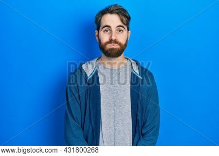 Caucasian man with beard wearing casual sweatshirt puffing cheeks with funny face. mouth inflated with air, crazy expression.
