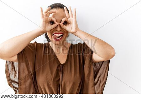 Young brunette woman standing over isolated background doing ok gesture like binoculars sticking tongue out, eyes looking through fingers. crazy expression.
