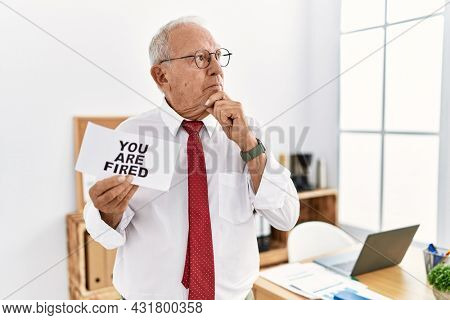 Senior business man holding you are fired banner at the office serious face thinking about question with hand on chin, thoughtful about confusing idea