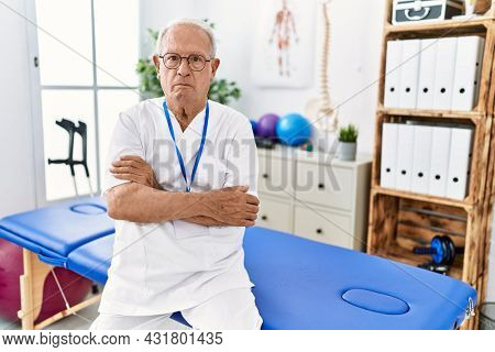 Senior physiotherapy man working at pain recovery clinic skeptic and nervous, disapproving expression on face with crossed arms. negative person.