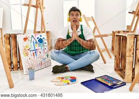 Young hispanic man at art studio begging and praying with hands together with hope expression on face very emotional and worried. begging.