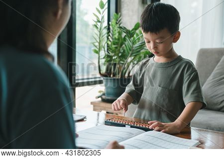 Asian Mother Teaching Child boy Learning Math With An Abacus, Education Concept, Home School, Socia