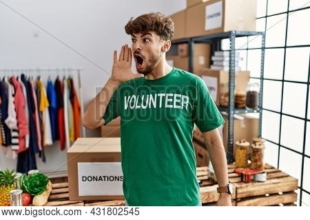 Young arab man wearing volunteer t shirt at donations stand shouting and screaming loud to side with hand on mouth. communication concept.