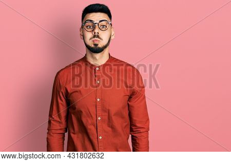 Young hispanic man with beard wearing business shirt and glasses puffing cheeks with funny face. mouth inflated with air, crazy expression.