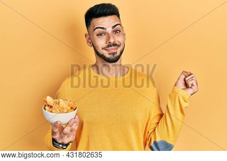 Young hispanic man with beard holding nachos potato chips screaming proud, celebrating victory and success very excited with raised arm