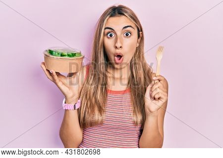 Beautiful hispanic woman eating salad afraid and shocked with surprise and amazed expression, fear and excited face.