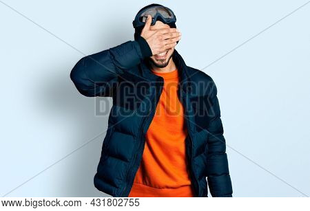 Young hispanic man with beard wearing snow wear and sky glasses smiling and laughing with hand on face covering eyes for surprise. blind concept.