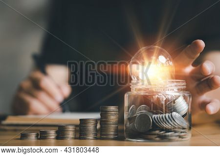 Businessman Holding Lightbulb With Using Calculator To Calculate And Money Stack. Idea Saving Energy
