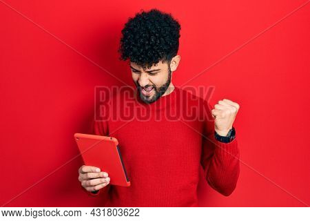 Young arab man with beard using touchpad device screaming proud, celebrating victory and success very excited with raised arms