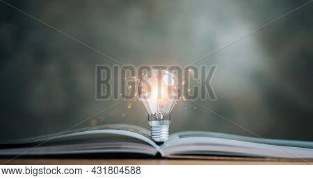 Light Bulb Glowing On Book, Idea Of inspiration From Reading, Innovation Idea Concept, Self Learni