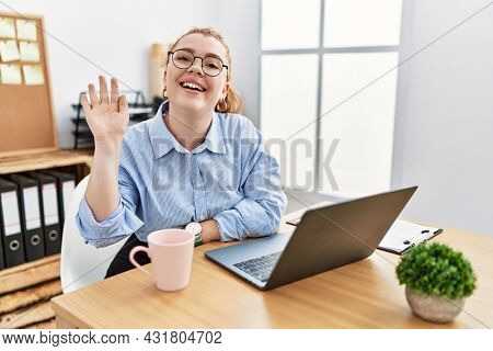 Young redhead woman working at the office using computer laptop waiving saying hello happy and smiling, friendly welcome gesture